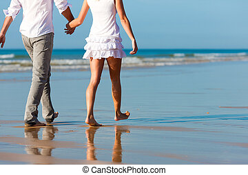 Couple in vacation having a walk under a perfect blue sky, they are embracing each other on shoulder
