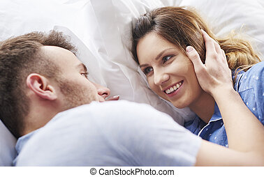 Couple head to head lying in bed together