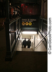subway - couple headed down the stairs of a subway station ...
