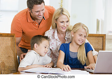 Couple helping two young children with laptop do homework in dining room