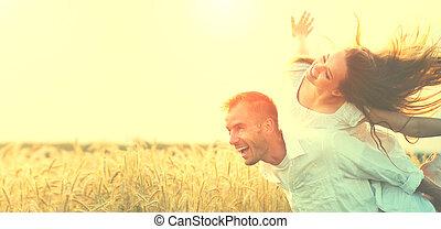 couple heureux, amusant, dehors, sur, champ blé, sur, coucher soleil