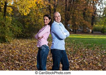 couple, heureux, armes traversés, jeune