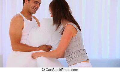 couple, heureux, jouer, oreillers