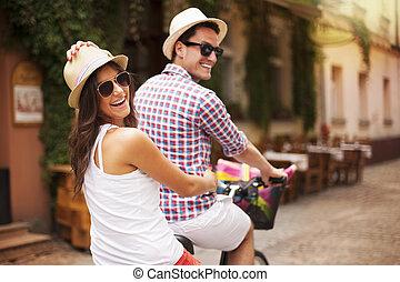 couple heureux, voyager bicyclette, dans ville, rue
