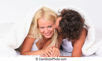 couple hiding under their blanket in the bedroom