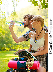couple hikers resting in forest drinking water