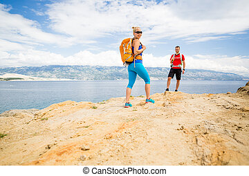 Couple hikers walking on trail at seaside