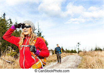 Couple hiking on trail in autumn forest
