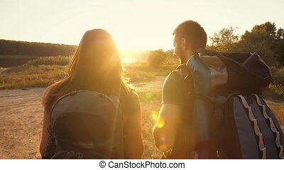Couple hiking with backpacks at sunset - Young man and woman...