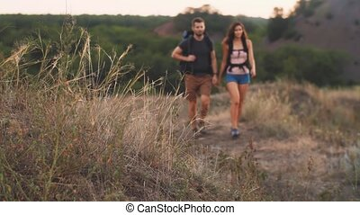 Couple hiking with backpacks - Young man and woman hiking...