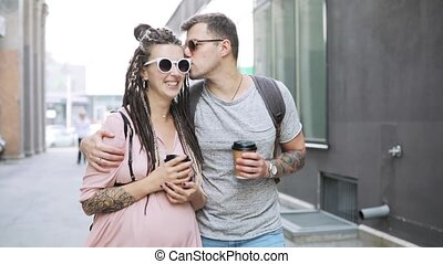 Couple hipsters man and pregnant woman walking in city with...
