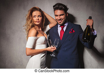 couple holding a bottle of champagne saying cheers - man...