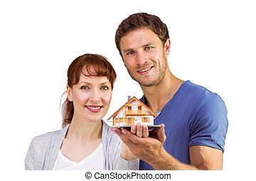 Couple holding a model house