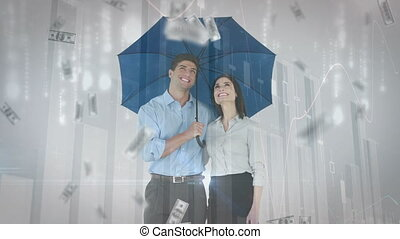 Couple holding an umbrella with money bills falling
