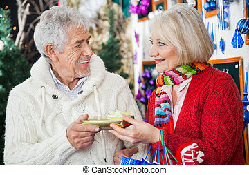 Couple Holding Christmas Gift At Store