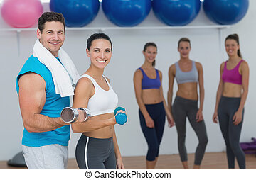 Couple holding dumbbells with fitness class in background