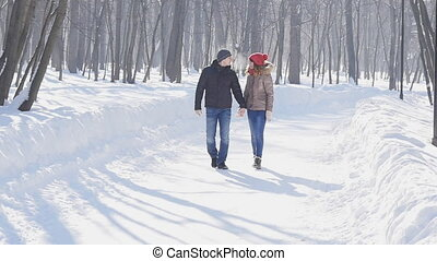 Couple holding each other's hands, the winter goes on the road