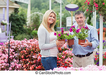 Couple holding flowers in garden center