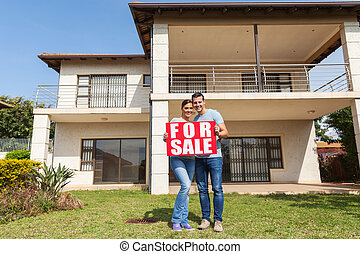 couple holding for sale sign in front of house