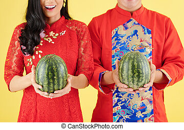 Couple holding fresh watermelons