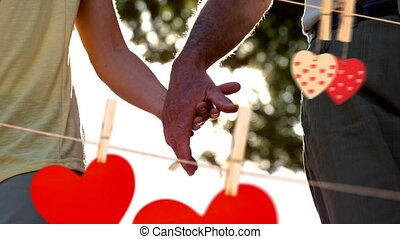 Couple holding hand on a sunny day with hearts for valentine day