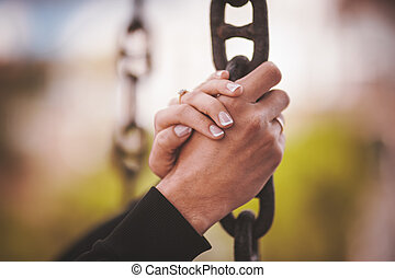 couple holding hand together on chain