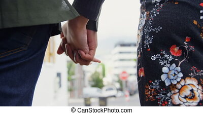 Couple holding hand while walking on street 4k
