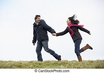 Couple Holding Hands And Running In The Park