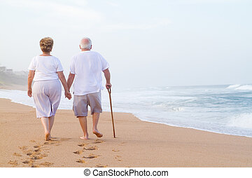 couple holding hands and walking on - a senior couple from ...