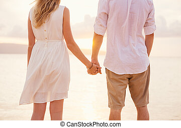 Couple holding hands at sunset on beach. Romantic young couple in love