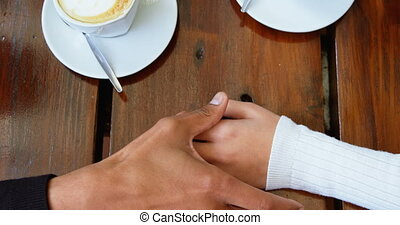 Couple holding hands in cafeteria 4k