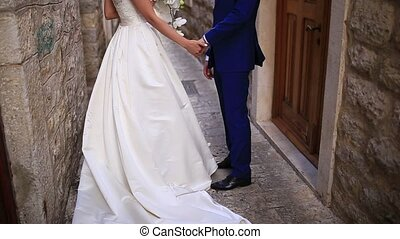 Couple holding hands in the old city. A newly married couple in