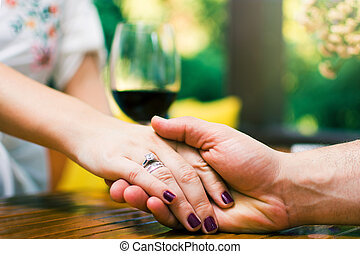 Couple holding hands on a date close up