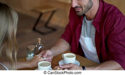 Couple holding hands on date in cafe