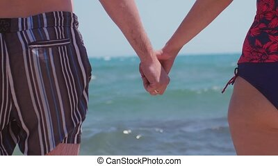 Couple holding hands on the background of the sea on the...