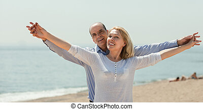 Couple holding hands on the beach - Happy elderly couple...