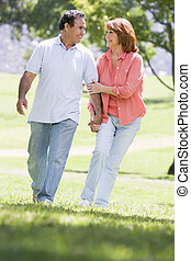 Couple holding hands outdoors by lake smiling