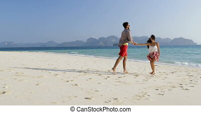 Couple Holding Hands Run To Water On Beach, Happy Smiling...