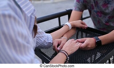 Couple holding hands sittings in the street cafe