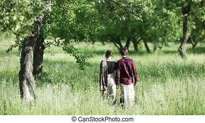 Couple holding hands walk in garden