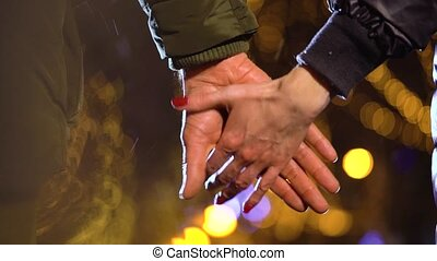 Couple holding hands, walking in night city - Close-up of a...
