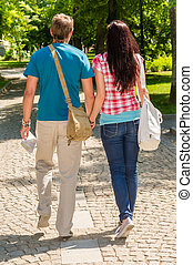 Couple holding hands walking in the park