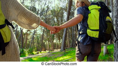 Couple holding hands while running in the forest 4k