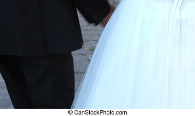 Couple holding hands while walking in the park near the old castle. Slow motion
