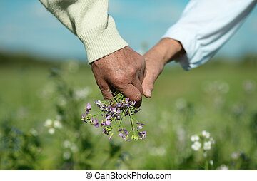 Couple holding hands with flowers