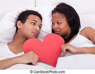 Couple Holding Heart - Portrait Of Young Couple In Bed...