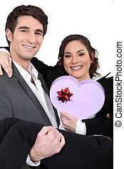 Couple holding heart-shaped box