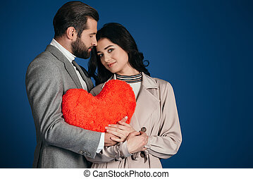 couple holding heart shaped pillow isolated on blue