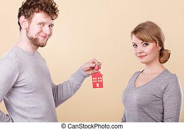 Couple holding key with house symbol