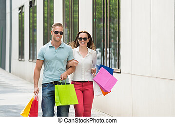 Couple Holding Multi-colored Shopping Bag - Couple Standing...
